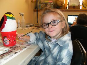 Autumn painting a Christmas ornament.
