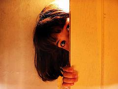 little-girl-peeking-from-behind-door