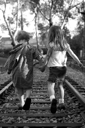boy-and-girl-holding-hands-on-railroad-track